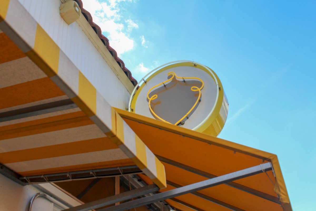 A picture of a yellow awning with an acorn logo in Bishop Arts District.
