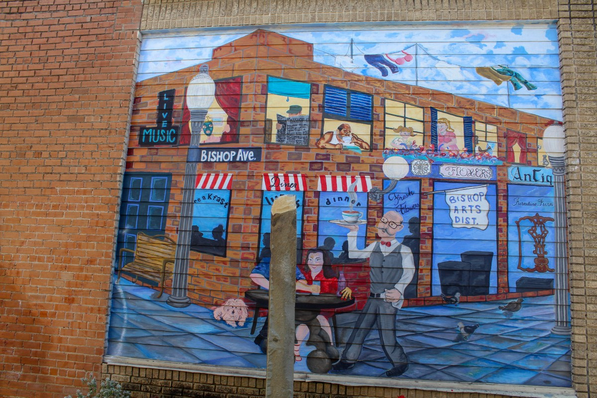 This street art wall in Bishop Arts District is a painting of a man carrying a cup of coffee towards a young couple in old Bishop Arts District. There's a street sign that shays Bishop Av and a man reading a newspaper in the window above.