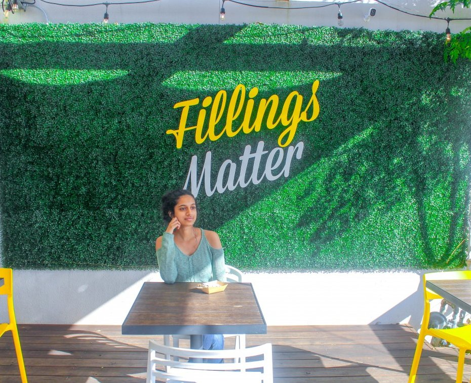 This is a snap of the famous Fillings Matter wall in Bishop Arts District. The wall is located at Picole Pops. It's a textured green with the word filling written in yellow.