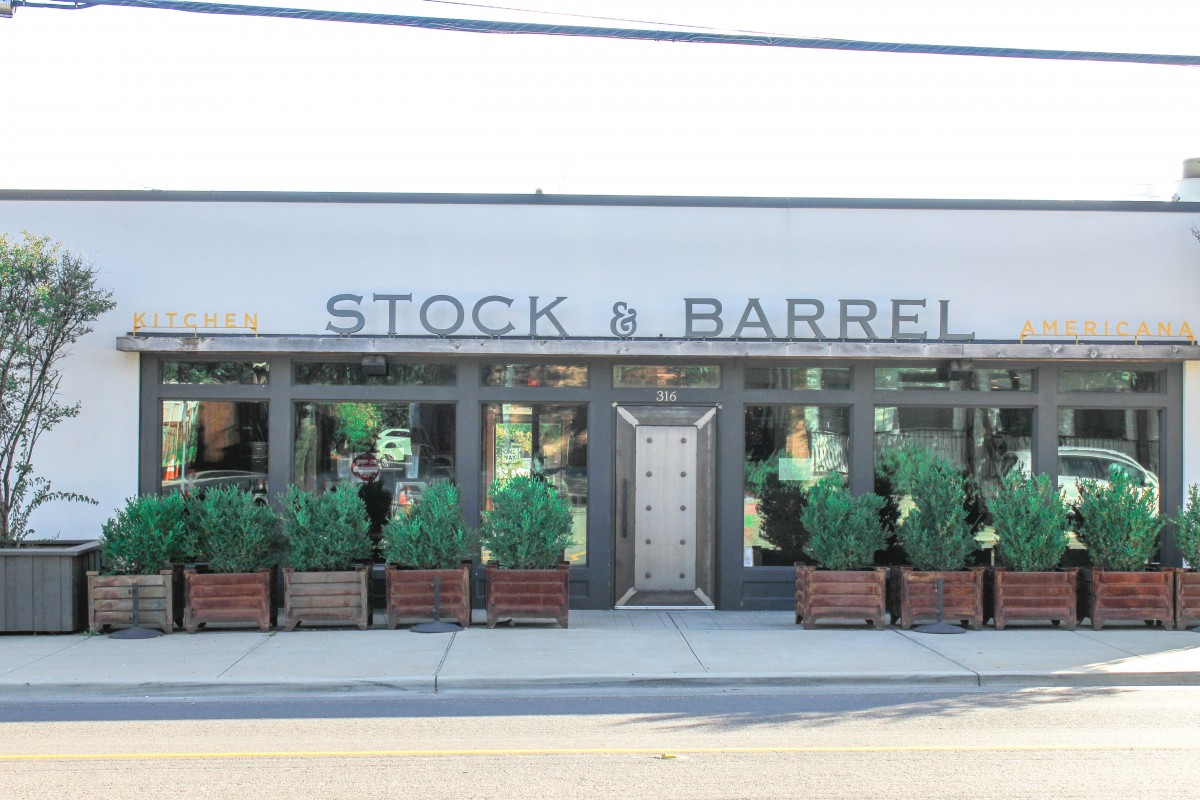 This is the entrance of Stock & Barrel in Bishop Arts District. It's a plain white building with several plants lined outside.