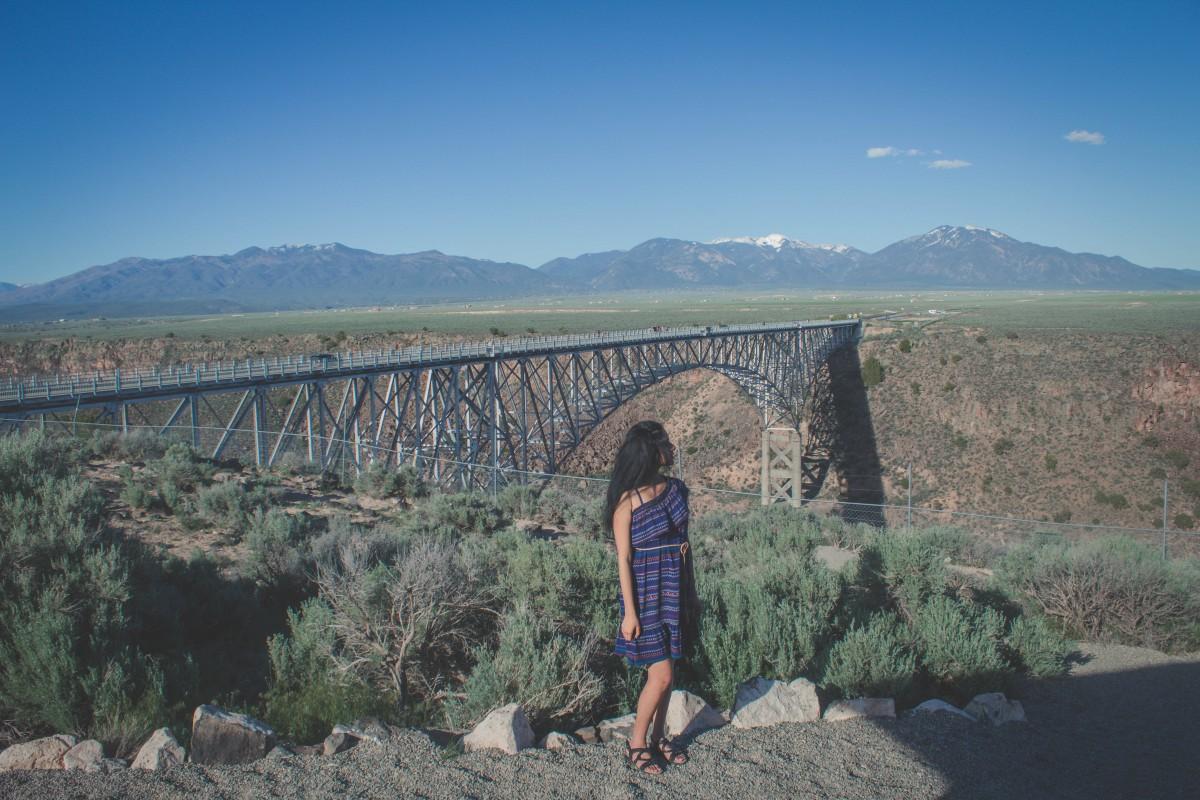 Girl in blue dress standing in front of Rio Grande Gorge Bridge.
