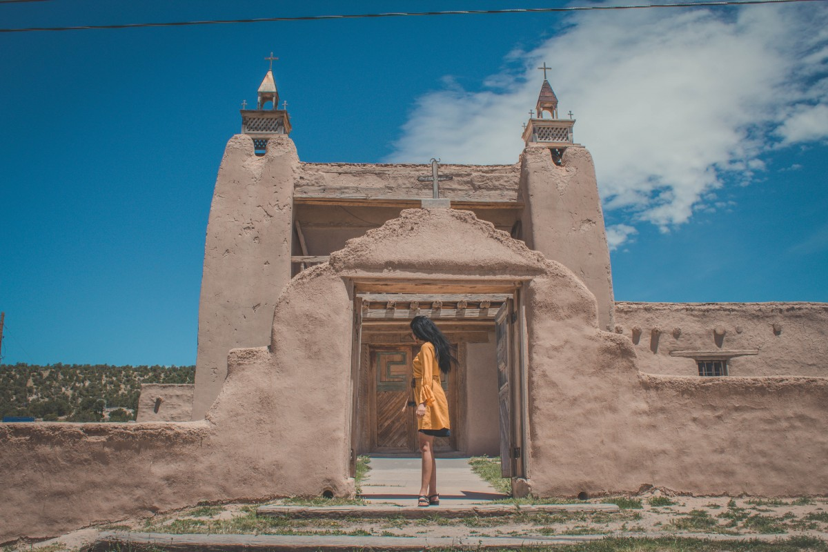 San Jose De Garcia Mission, a church in between Santa Fe and Taos. Girl in bright yellow dress standing to the side by the steps of the mission. You can see the sun-baked adobe.
