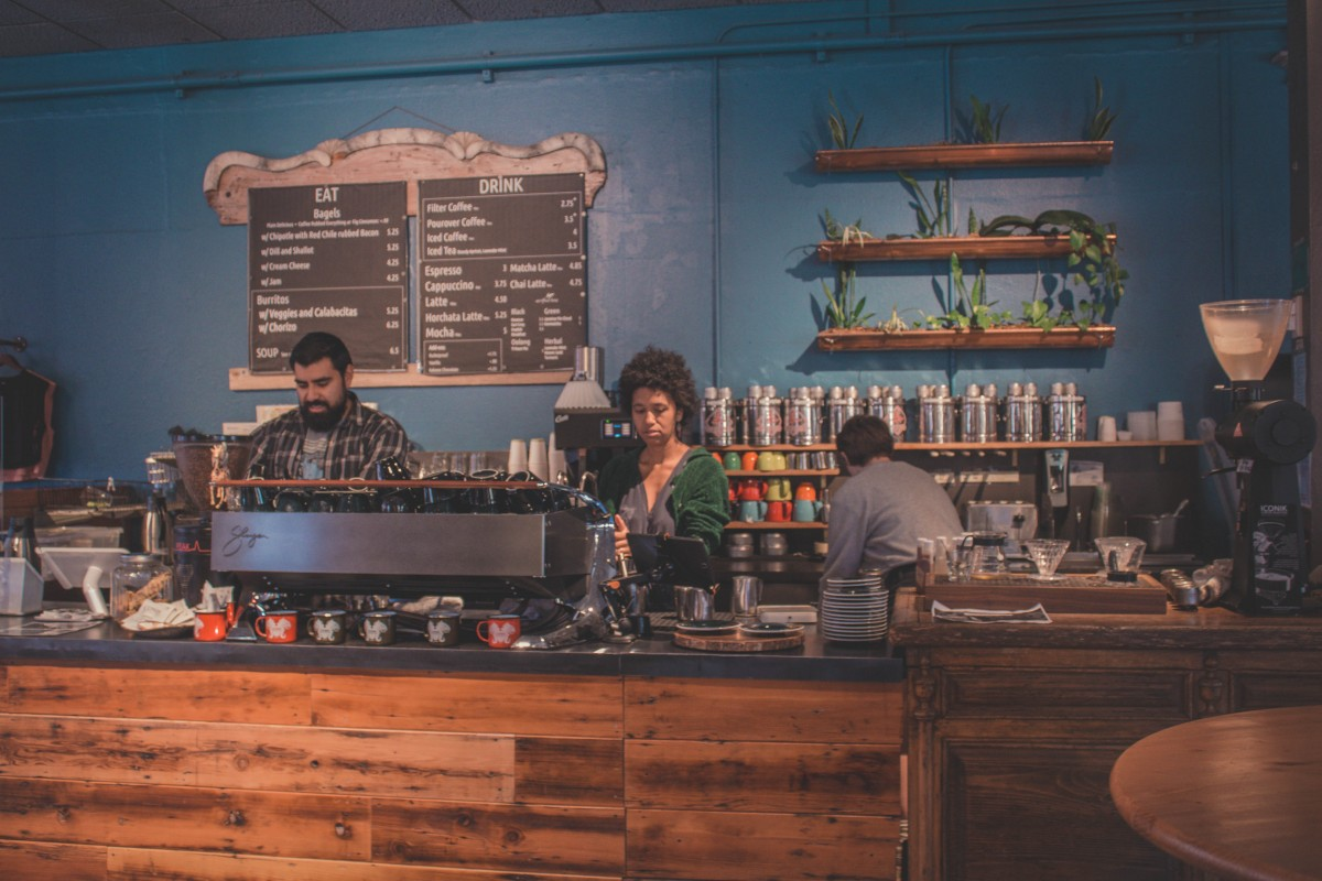 Coffee bar against a deep blue wall in Collected Works in Santa Fe. There are three baristas shown.