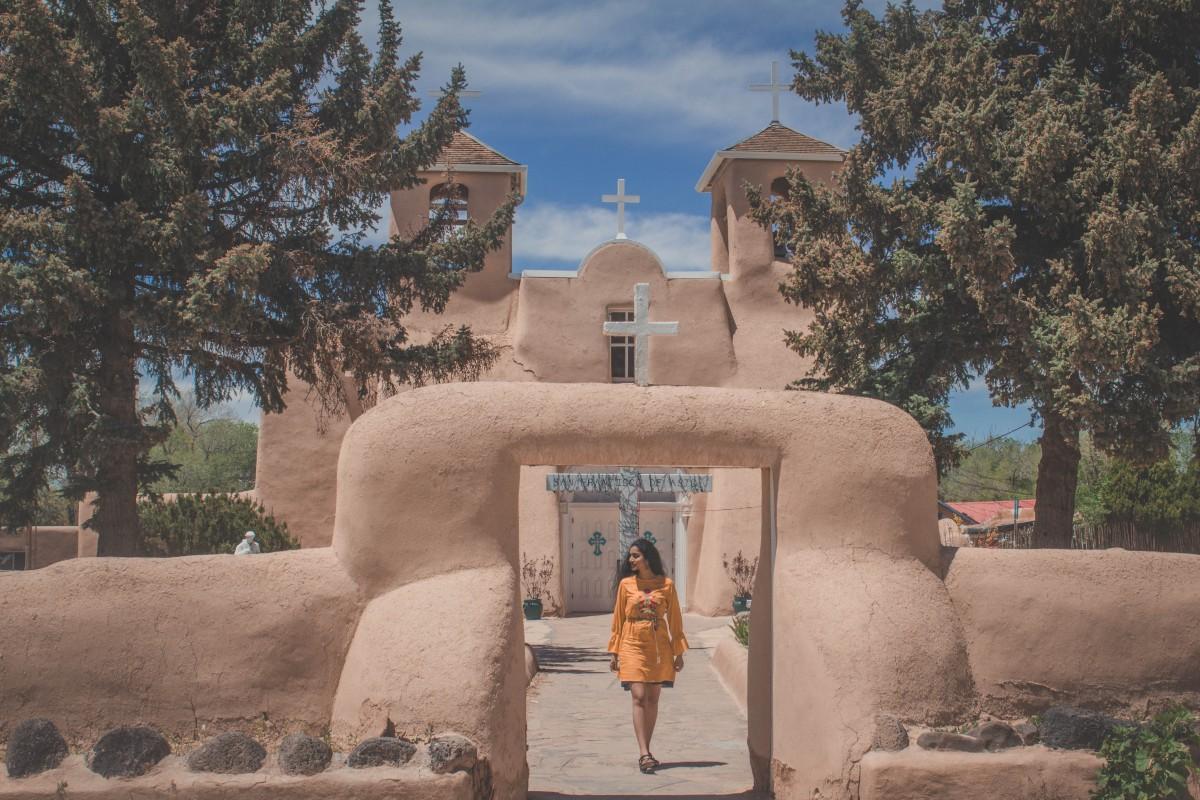 Girl in yellow dress walking in front of San Francisco De Asis Church in Ranchos De Taos, one of the last stops between a Santa Fe to Taos road trip.