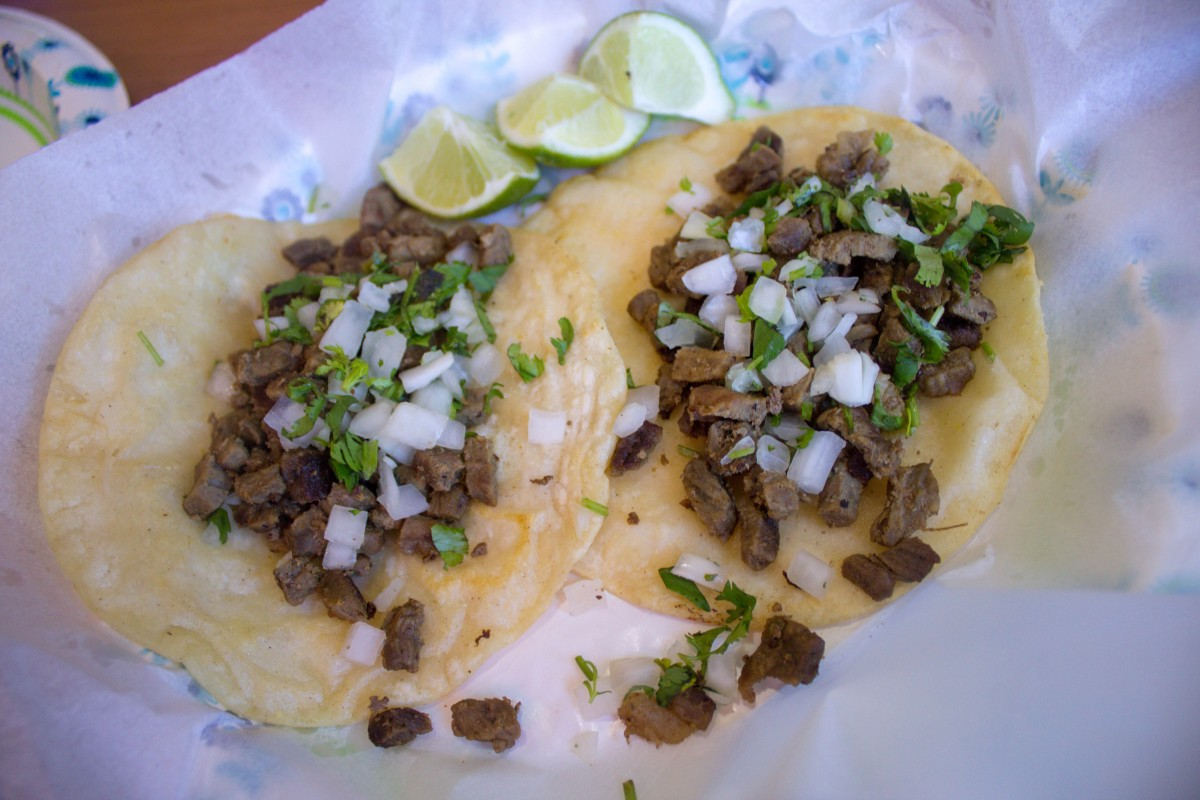 Meat on deep fry bread tacos and lime wedges next to the tacos. Fry bread is one of the oldest traditional New Mexican foods.