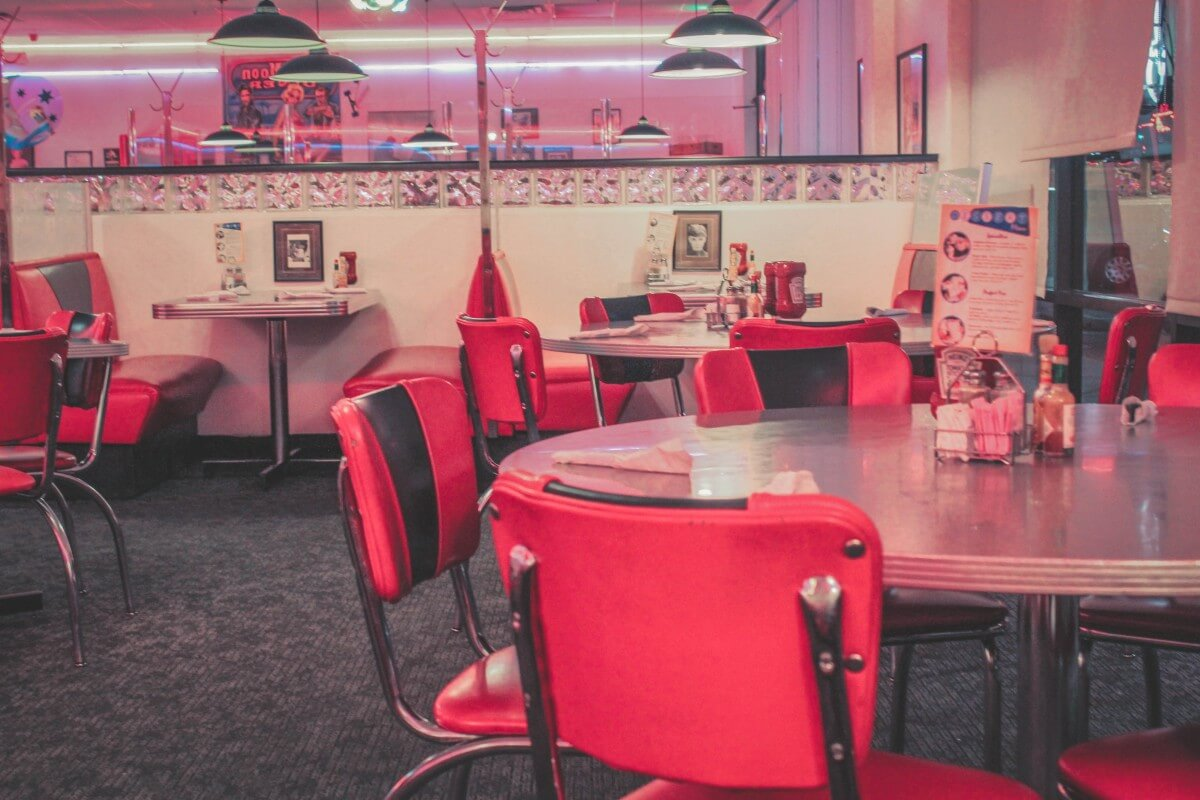 Retro pink diner (Blue Moon Diner) with red chairs and pink lights.