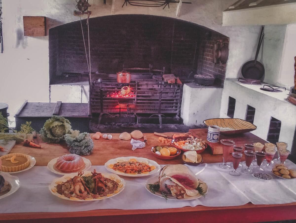 A full spread of food in Colonial Williamsburg. There's desert pie and meat and raw veggies that still need to be prepared and plenty of drinks.