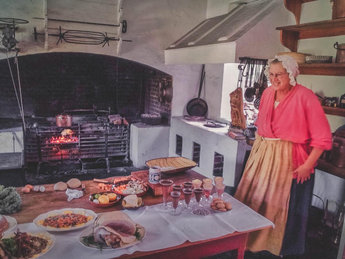 a woman, dressed in period clothing, smiles in front of a full feast of food at one of the cooking demonstrations in Colonial Williamsburg. She's wearing a bonnet and there's a fire in the back heating up food.