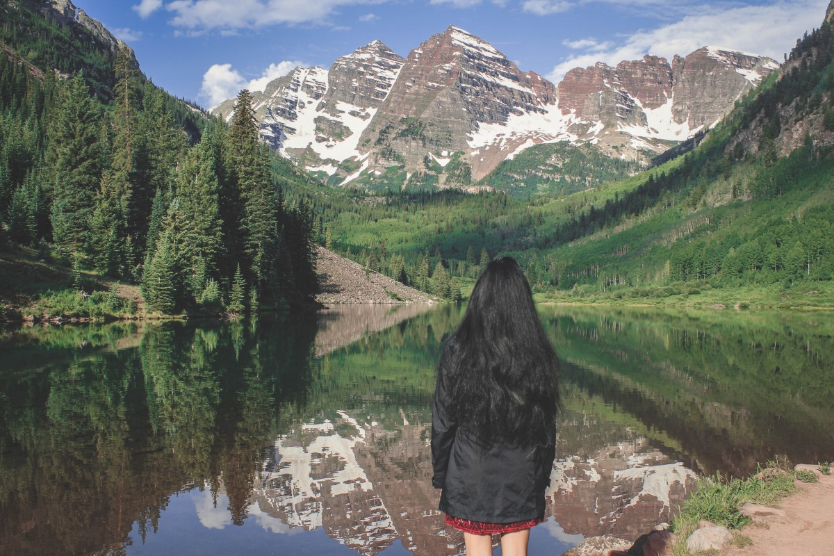 Girl standing in front of Maroon Bells in Colorado