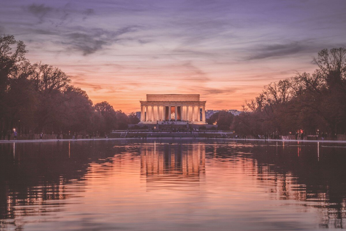sunset in DC facing the Lincoln memorial at night. The statue of Lincoln is softly glowing.