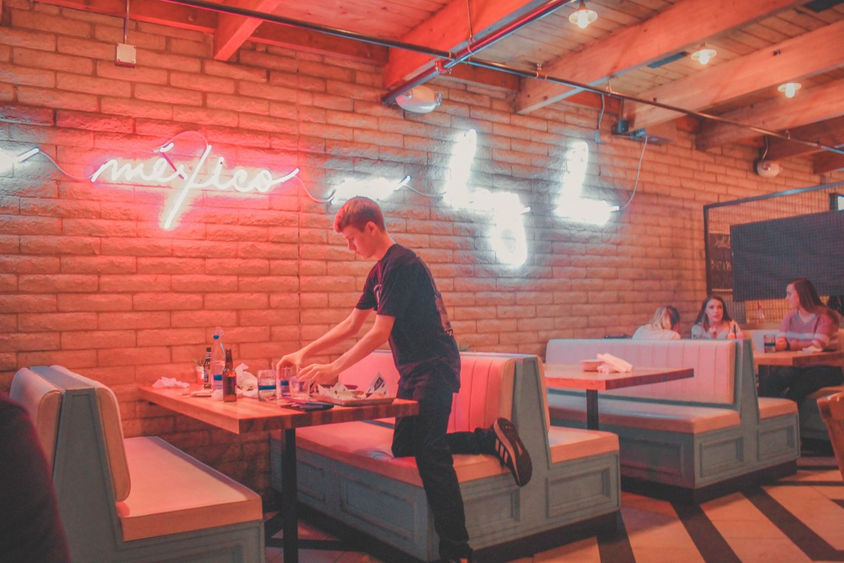 Waiter cleaning up a table at Diego Pops, a bright pink eatery in Scottsdale.