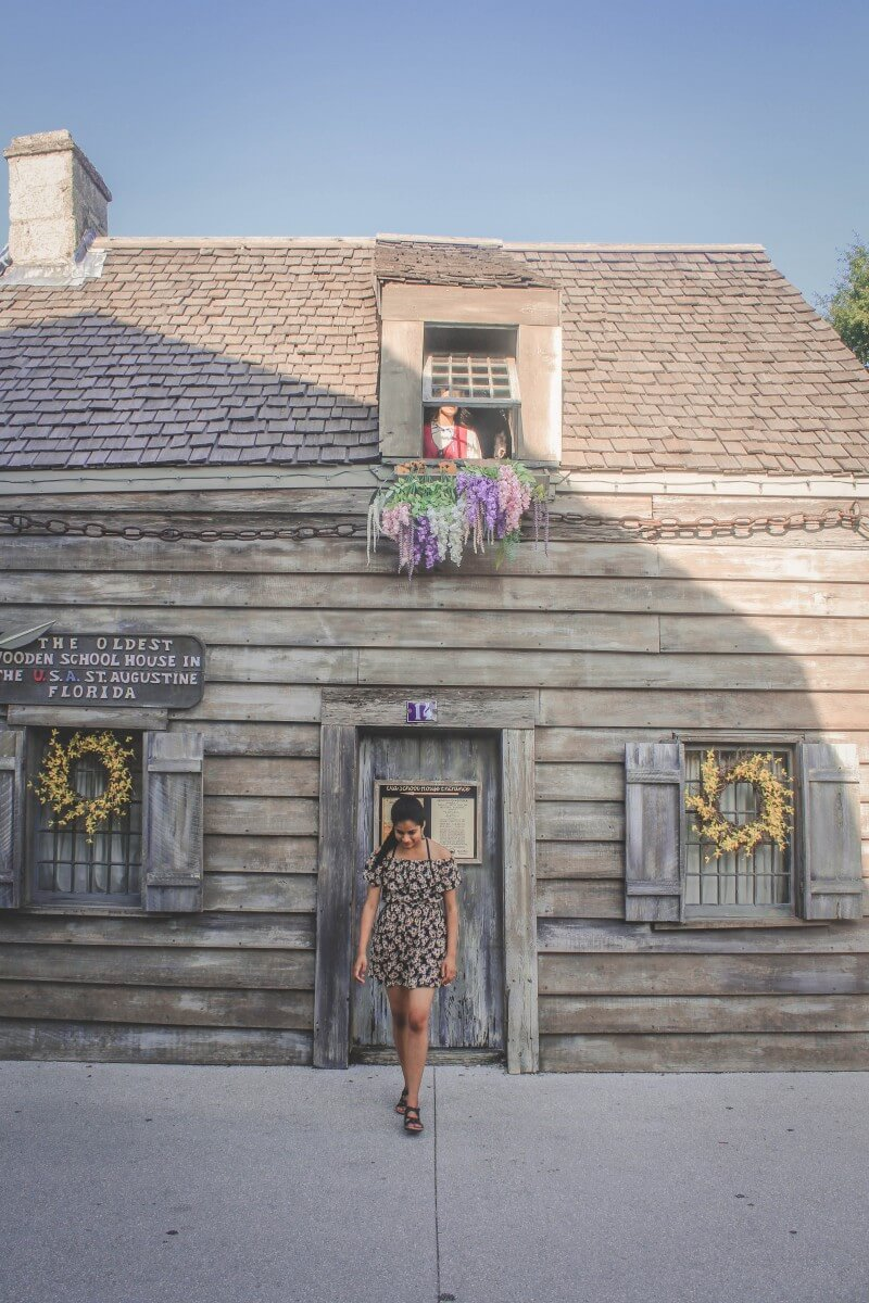 Girl walking in front of the oldest wooden schoolhouse (one of the animatronic displays is up top)