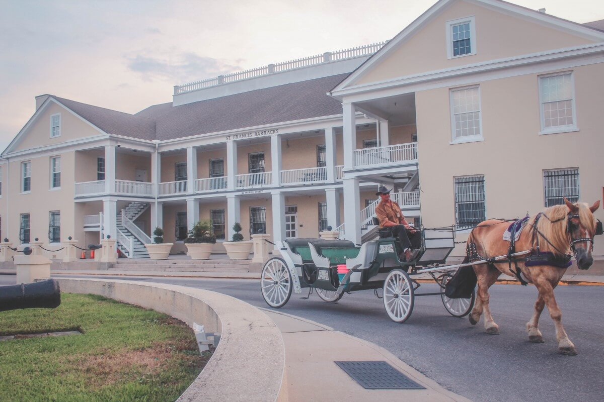 Soft yellow walls of the Saint Francis Barracks. A horse-drawn carriage is being pulled forward in front.