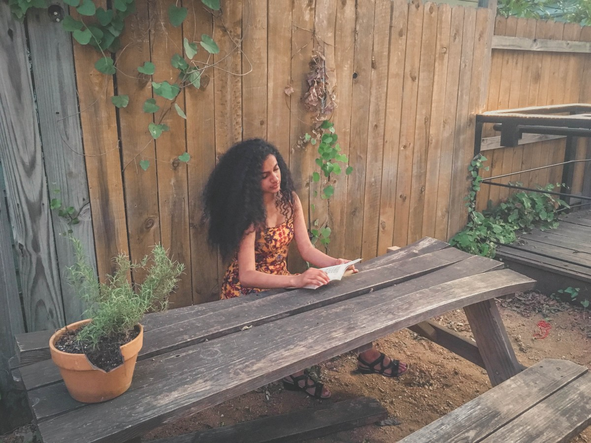 girl with richly thick curly locks reading a book while traveling