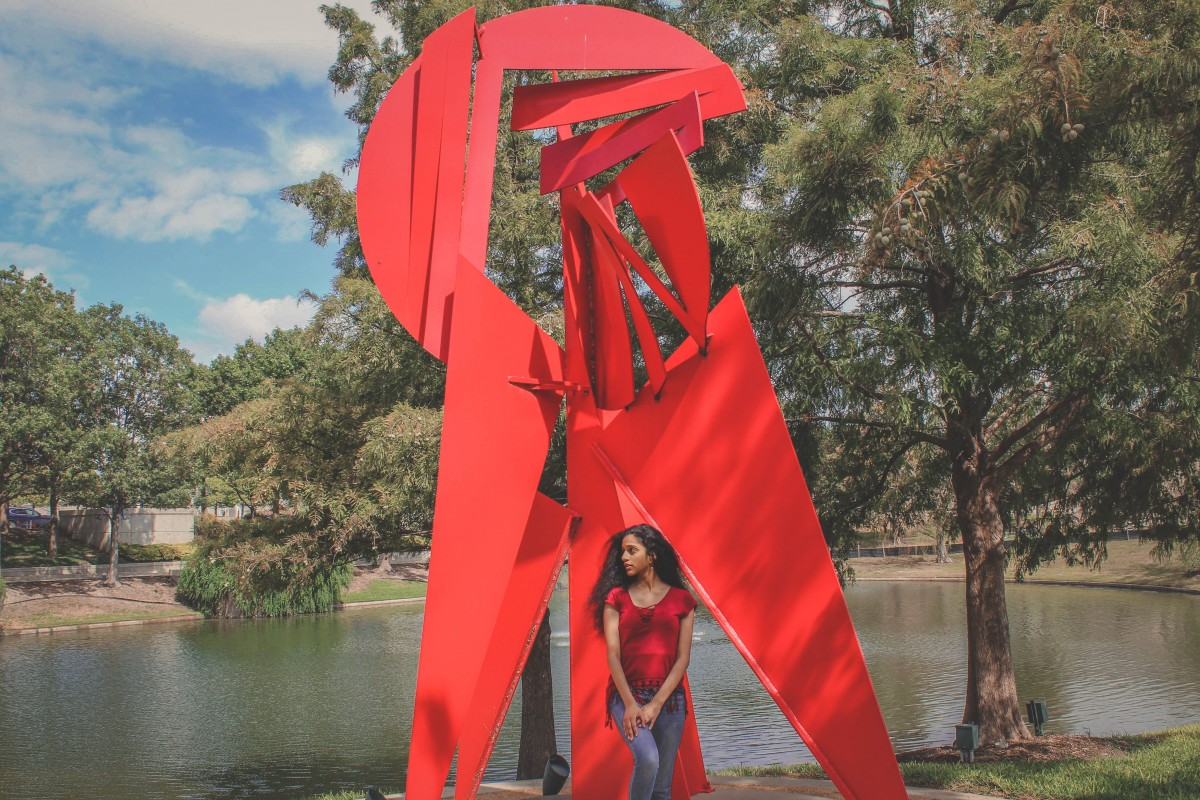 person in front of Texas Sculpture Garden red sculpture in Frisco