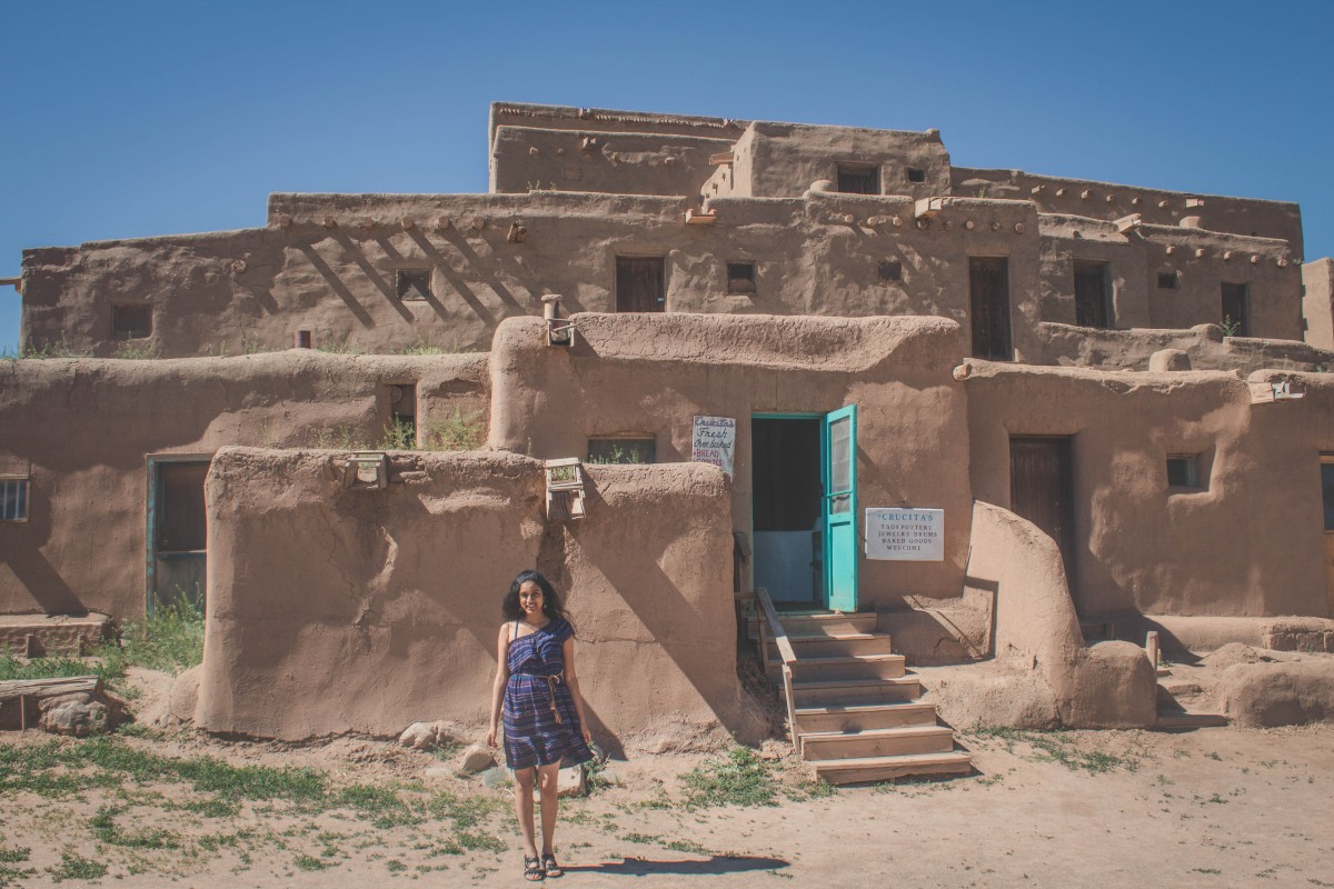Anshula standing in front of the adobe of Taos Pueblo in Taos