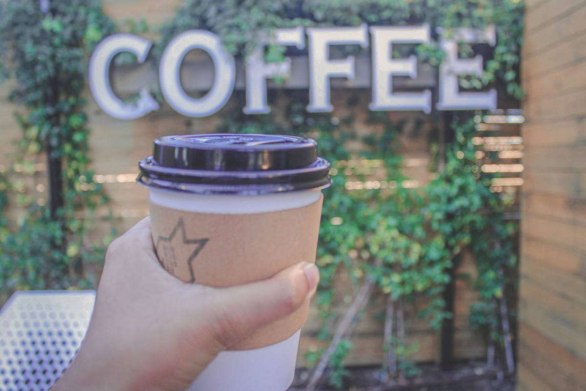 holding a cup of coffee in front of a coffee sign