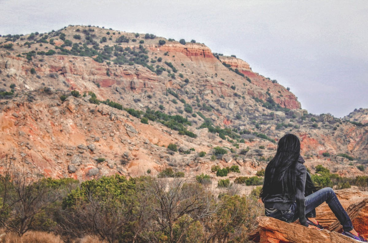 girl sitting on a ledge looking at Palo Duro Canyon
