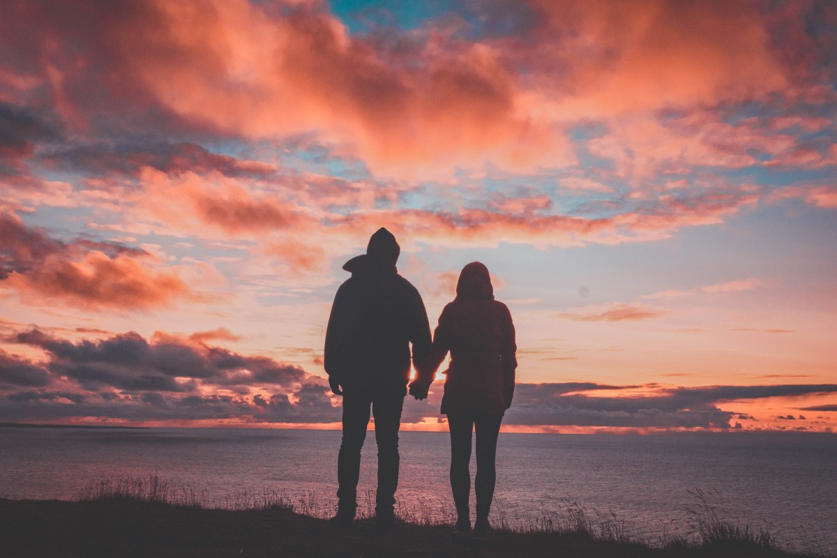 road trip questions for couples - couple holding hands at sunset