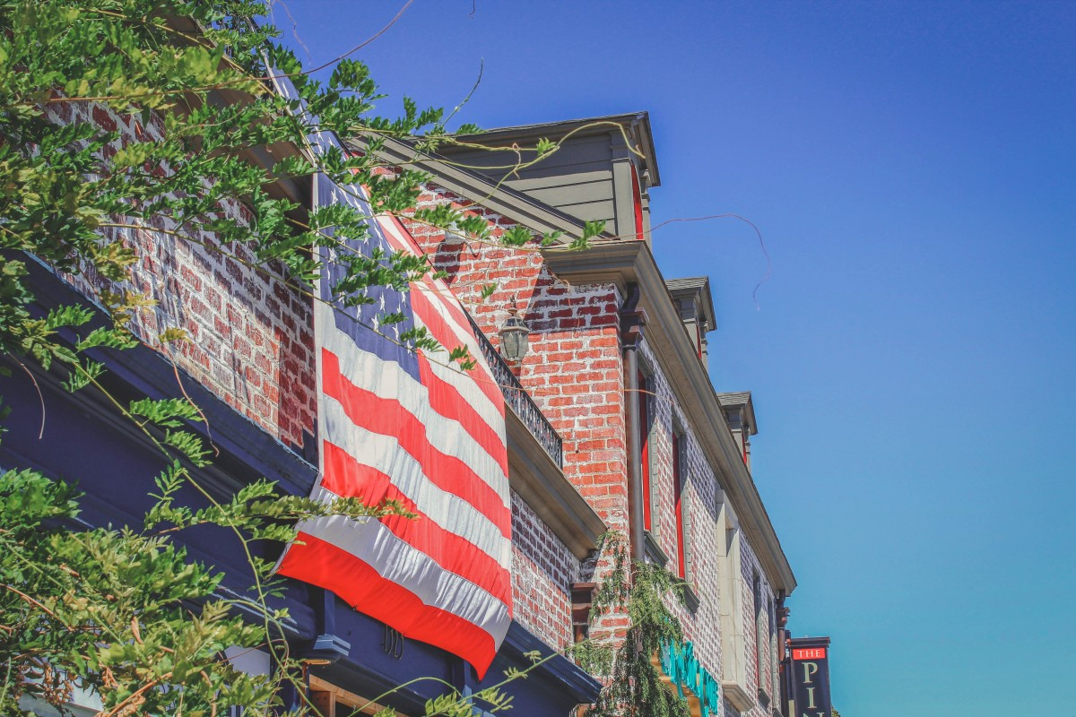 old photo of Cherry Street, brick-front with American flag