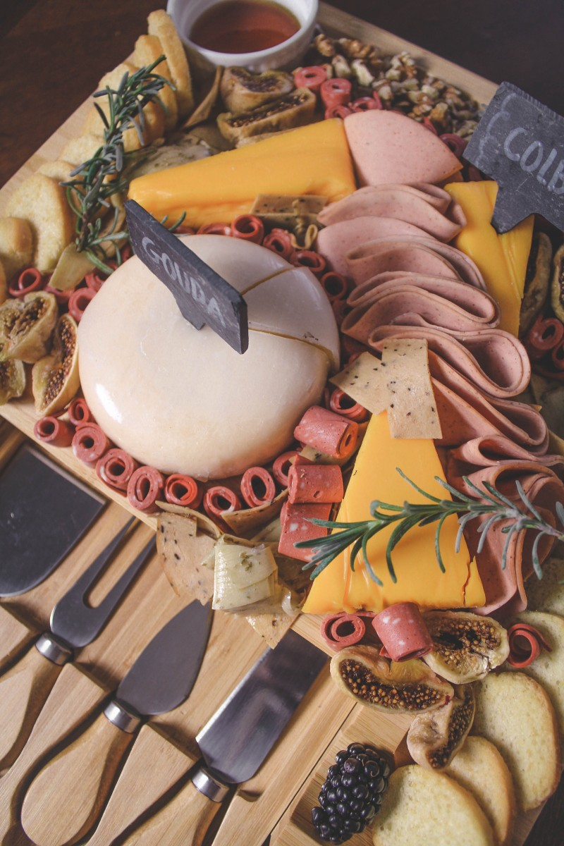 Vegetarian Charcuterie Board ingredients laid out. Photo shows cheese and vegan salami and nuts.